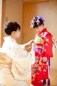 自宅で七五三の着付けをする母親と女の子