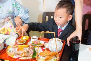 七五三のお祝い御膳に喜ぶ5歳の男の子